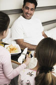 Girls giving father breakfast in bed — Stock Photo