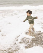 Boy splashing through ocean surf — Stock Photo