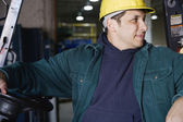 Man in warehouse holding steering wheel — Foto de Stock