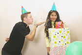 Young man blowing confetti on birthday girl — Stock Photo