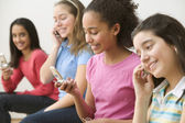 Four girls sitting with cell phones — Stock Photo
