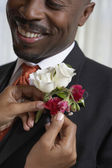 Woman pinning flowers onto man's lapel — Stock Photo