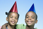 African brother and sister wearing party hats — Foto de Stock