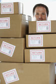 Studio shot of man behind returned packages — Stock Photo