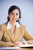 Hispanic businesswoman wearing headset — Stock Photo