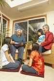 Asian grandfather reading a book to his granddaughters — Stock Photo