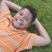 Indian boy laying in grass smiling — Stock Photo