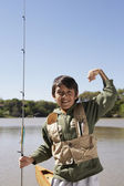 Hispanic boy holding fishing pole outdoors — Stock Photo