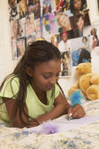 Teenage girl writing in journal — Stock Photo