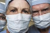 Close-up dos seniores masculinos e femininos médicos em máscaras cirúrgicas — Fotografia Stock