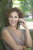 Hispanic woman talking on cell phone outdoors — Stockfoto