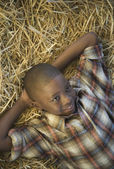 African boy laying in hay — Stock Photo