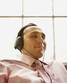 Uomo d'affari rilassanti ascoltando le cuffie — Foto Stock