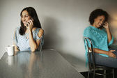 Two women talking in cafe on cell phones — Stock Photo