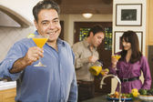 Middle-aged Hispanic man toasting with cocktail — Stock Photo