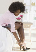 African woman putting on high heels — Stock Photo