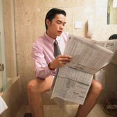 Businessman reading newspaper while sitting on toilet — Stock Photo