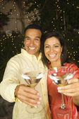 Hispanic couple toasting with cocktails at night — Stock Photo