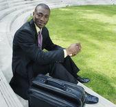 бизнесмен с портфель, сидя на открытом воздухе — Стоковое фото