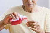 Bliska starszy kobieta odlewania leków do kubka — Zdjęcie stockowe