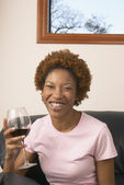 Portrait of young woman holding glass of wine — Stock Photo