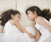 Two young Hispanic sisters lying in bed — Stock Photo