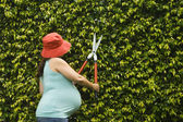Pregnant woman using hedge clippers — Stock Photo