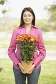 Portrait of Hispanic woman holding potted plant — Stock Photo