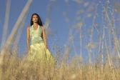 Mulher caminhando entre gramíneas selvagens — Fotografia Stock