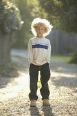 молодой мальчик, стоя на гравий пути — Стоковое фото