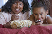 African mother and daughter eating popcorn — Stock Photo