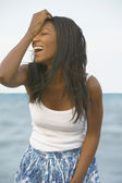 Young African woman laughing at the beach — Stock Photo