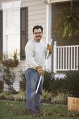 Man raking leaves in front yard — Stock Photo