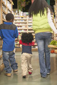Mother with young sons in health food store — Stock Photo