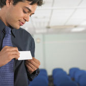 Businessman attaching name tag to jacket — Stock Photo