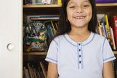 Girl standing in front of bookshelves — Stock Photo