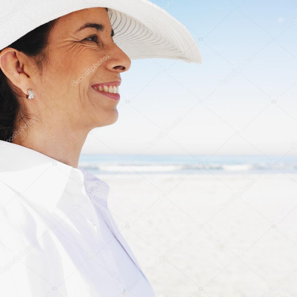 Hispanic woman wearing sunhat at beach — Stock Photo #13230726