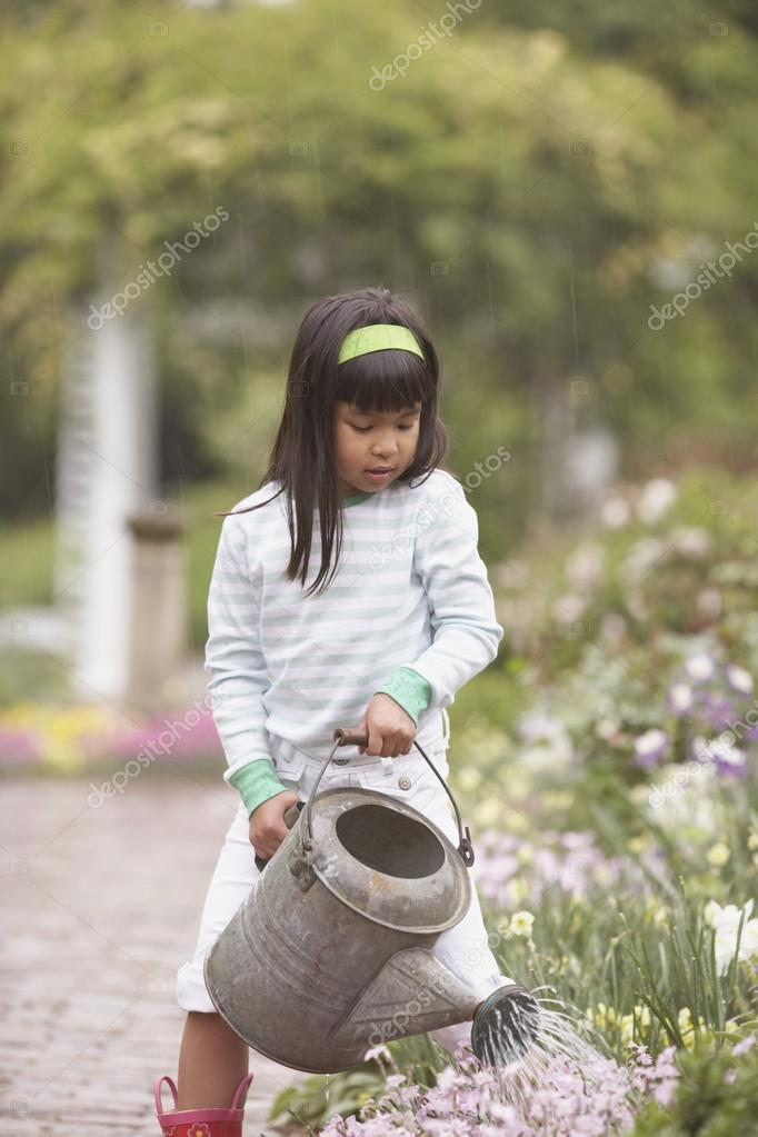 Asian girl using watering can in garden — Lizenzfreies Foto #13234645