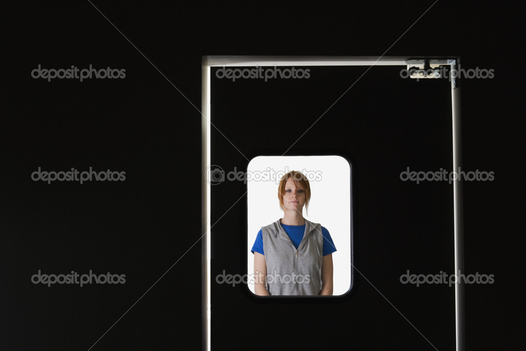 Woman standing behind door window — Stock Photo #13235098