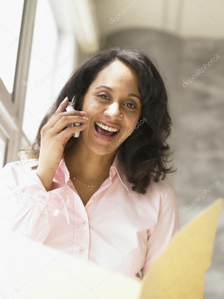 Businesswoman talking on her cell phone as she examines a folder — Stock Photo #13235447