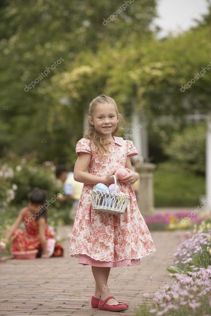 Young girl with Easter basket in garden — Stock Photo #13238140