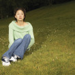 Stock Photo: Womsitting in grassy field