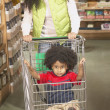 African American mother pushing young son in shopping cart — Stock Photo