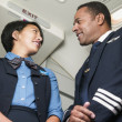 Flight attendant looking at pilot - Stock Photo