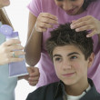 Two teenage girls styling teenage boy's hair — Stock Photo