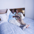 Senior African couple watching television in bed — Stock Photo