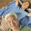 Stock Photo: Senior couple relaxing on a blanket outdoors