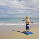Boy standing on boogie board at beach — Stock Photo