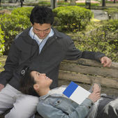 Asian couple sitting on park bench with guide book — Stock Photo
