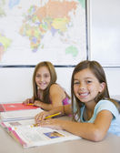 Two girls smiling at desk in classroom — Stock Photo